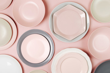 Plates and dishes for serving a festive table on pastel colors background. Flat lay, top view.