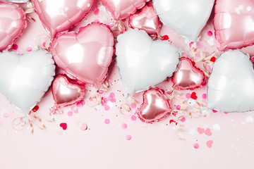 Air Balloons of heart shaped foil  on pastel pink background. Love concept. Holiday celebration....