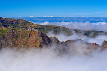 Mountain peaks in the clouds against clear blue sky. Portuguese island of Madeira