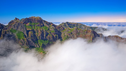 Mountain peaks in the clouds against blue orange sky. Portuguese island of Madeira