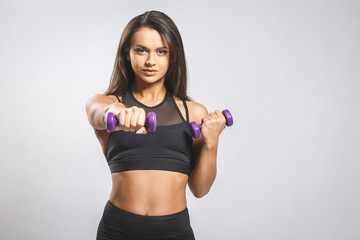 Enjoy your body! Beautiful young woman doing exercises with dumbbells at biceps. Photo athletic woman with perfect body isolated on white background. Strength and motivation, close-up.