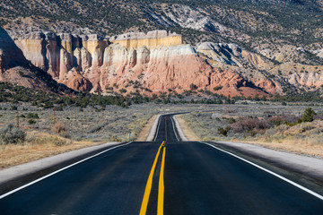 Highway curving into the distance toward colorful cliffs in near Abiquiu, New Mexico in the American Southwest