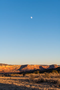 Moon over a colorful desert landscape at dusk over Ghost Ranch in Abiquiu, New Mexico