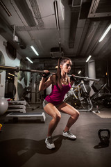 Sporty beautiful woman doing squats and holding weight bar on shoulders in a gym. In backgroung exercise equipment.