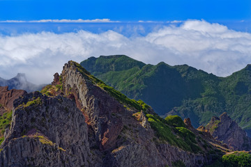 Panoramic view of mountain peaks against clouds below horizon and clear blue sky on sunny day