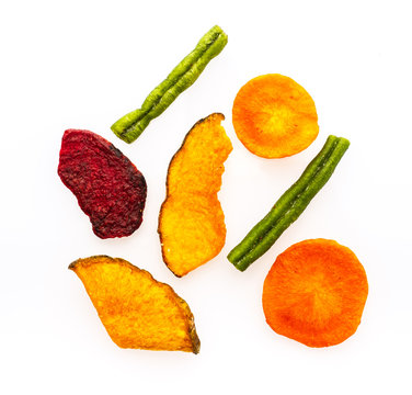 Dried vegetables chips from carrot, beet, parsnip and other vegetables isolated on white background. Organic diet and vegan food