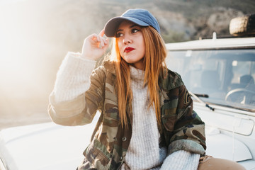 Young woman on casual wear touching cap and sitting on car