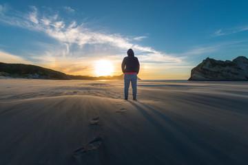 New Zealand, South Island, Puponga, Wharariki Beach, Woman on the beach at sunset