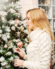 woman in white sweater stands near a Christmas tree