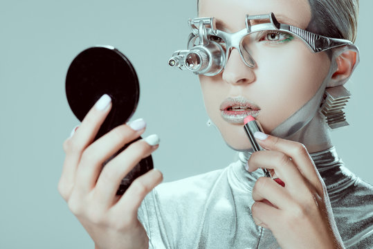 silver robot looking at mirror and applying lipstick isolated on grey, future technology concept