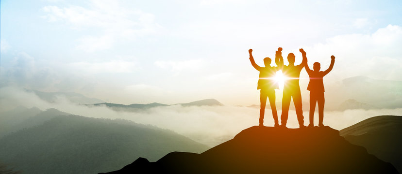 Silhouette of Business team show arm up on top of the mountain. Leadership and success Concept.