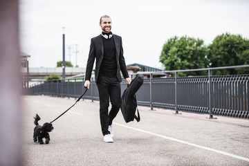 Fashionable young man holding guitar case walking with dog on a bridge