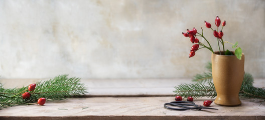 rosehips and fir branches in a stoneware vase and on a rustic wooden table to arrange christmas decoration, vintage background with copy space, panoramic banner format
