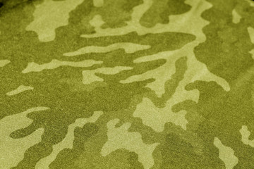 Old camouflage cloth with blur effect in yellow tone.
