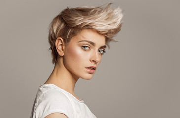 Self adhesive Wall Murals Hair Salon Portrait of young girl with blond fashion hairstyle looking at camera isolated on gray background