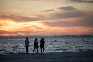 silhouettes of people after sunset at the beach