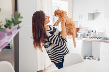 Young woman playing with cat in kitchen at home. Girl holding and raising red cat