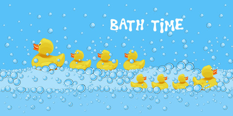 Set of cute rubber duck toys swimming in the bath water with soap bubbles.