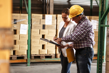 Female manager and warehouse worker checking list and inventory on the shelf in storehouse.