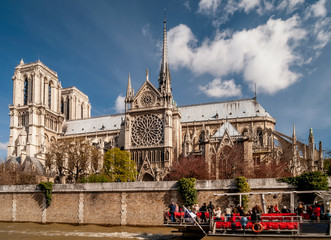 The Cathedral of Notre Dame in Paris, France, with a boat of tourists in the foreground
