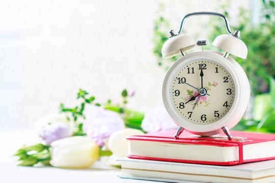 Retro alarm clock, notebook and spring flowers.