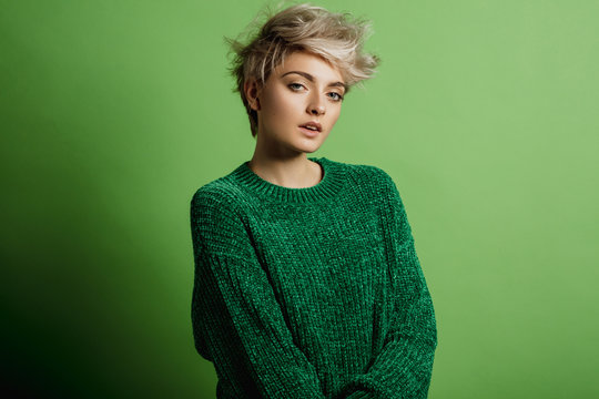 Fashion portrait of young woman with blond short hair isoalted on green background