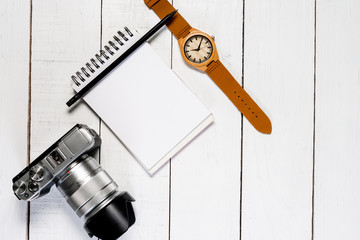 Camera on white wooden background. Notepad with white space and clock.
