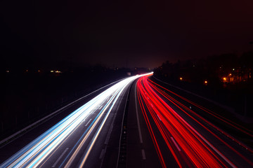 Light trails of cars at night on a highway