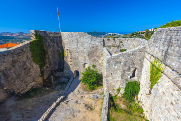 The courtyard of the fortress surrounded by high stone walls, the national flag hoisted at the corner of an ancient building. Summer landscape in Fortress Old Bar Town, Montenegro.