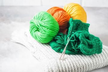 Green knitting yarn and knitting needles close-up.