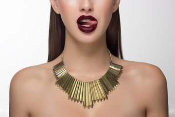 Close up glamorous image of a female predator with licking marsala lips. On the neck of the girl gold jewelry. Beautiful transparent skin, laminated hair. Spa care or beauty care. Beauty sexy woman