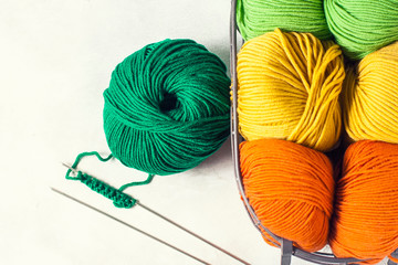 Different colored yarn in a basket with a knitting needle. The concept of knitting and needlework.