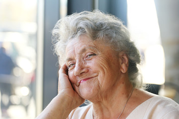Smile and looking elderly woman portrait on a light background