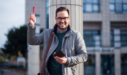 Portrait of happy business man holding credit card