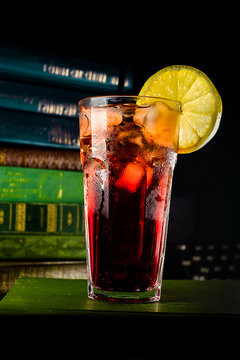 Closeup glass with ice cubes, dark red drink and lemon on edge. Vintage background with books.