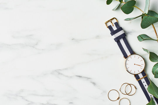 Women's watch with navy blue and white nylon strap, golden rings and eucalyptus on white marble background. Top view with copy space for text.