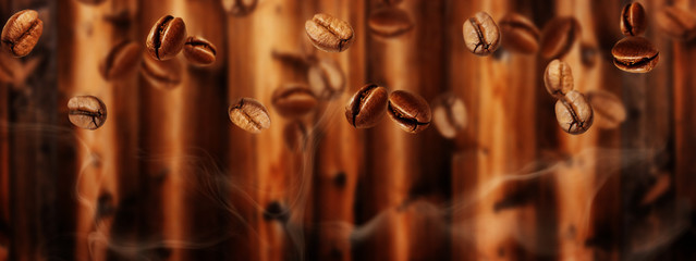 Flying coffee beans in front of dark brown wood, banner