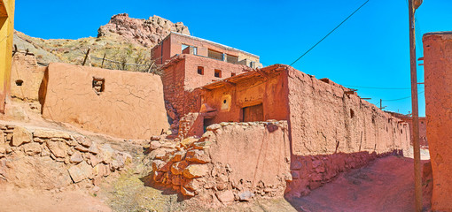 The shabby walls of medieval mud houses of Abyaneh village with the ruins of ancient fort on the mountain top, seen on the background, Iran.