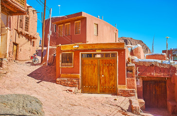 The narrow curved street leads to the mountain top, running among the restored old red-ochre houses of local villagers, Abyaneh, Iran.