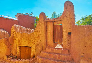 Preserved medieval gate of red clay leads to the tiny private garden, Abyaneh village, Iran.