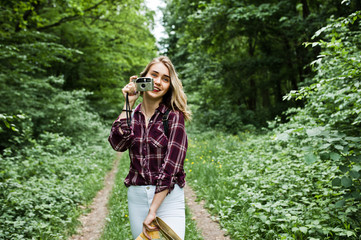 Portrait of a gorgeous young girl in tartan shirt taking pictures with camera in the forest.
