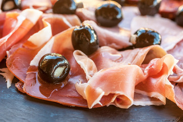 Slices of Spanish Jamon Iberico and olives