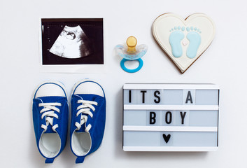 """fla tlay pregnancy composition with space for text on white background. top view of children's accessories: snickers, pacifier, baby screen, baby projector lamp """"it's a boy"""", delicious gingerbread"""