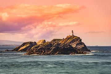 Lighthouse at beautiful Faeroe islands during magical sunset, summer time