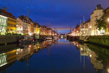 Panoramic view of Nyhavn with colorful facades of old houses and old ships in the Old Town of Copenhagen, capital of Denmark.