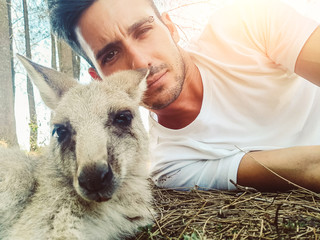 Handsome tourist man taking a self portrait with a kangaroo at vacation, Australia
