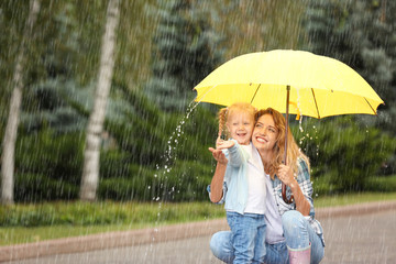 Portrait of happy mother and daughter with yellow umbrella in park on rainy day. Space for text