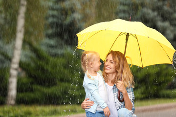 Obraz Portrait of happy mother and daughter with yellow umbrella in park on rainy day. Space for text - fototapety do salonu