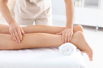 Woman receiving leg massage in wellness center, closeup