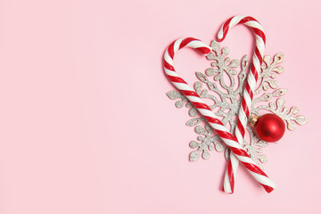Flat lay composition with tasty candy canes and space for text on color background